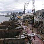 Dump scows SE103 and SE104 shown during an extensive re-fit in Boston, MA during the summer of 2005.  The SE103 and SE104 are six pocket bottom dump scows. Their dimensions are 170ft. long by 43ft wide with a moulded depth of 16 ft.