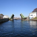 """""""Threading the Needle""""     Here the""""26"""" pushes a loaded dump scow through the Blyman Bridge during the dredging of the Cape Ann Marina.  Scows had only 1 foot of clearance on these openings."""